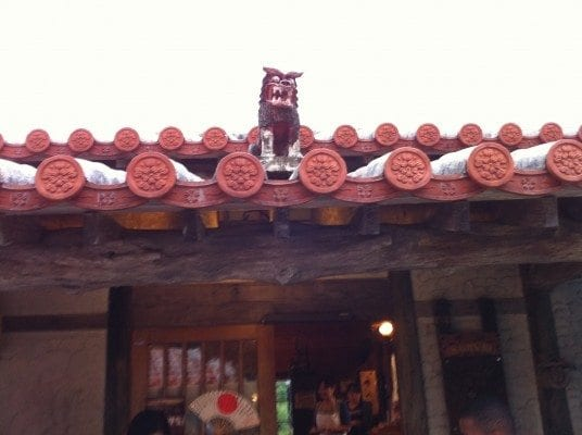 A Shisa sits on top of an Okinawan roof