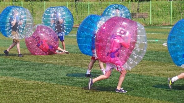 Bubble ball participants in action on the field.