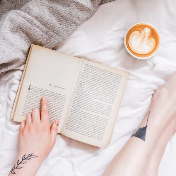 Woman reading a book with a cup of coffee