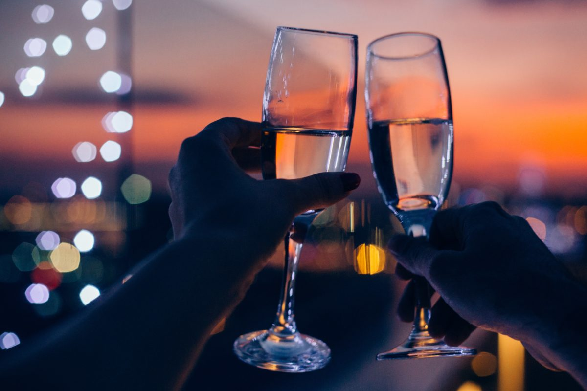 Hands holding glasses of champagne , city in sunset in background
